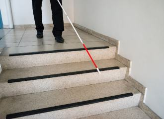 A blind man is using a long white cane and approaches some steps