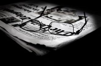 A pair of glasses on a newspaper
