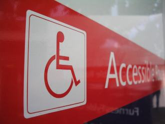 Red sign with wheelchair symbol and accessible route text