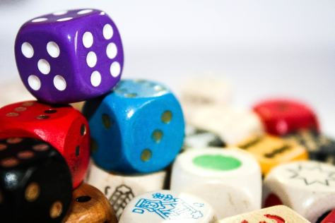 several different coloured dice in a pile
