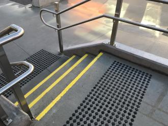 Yellow stair tread nosing strips on wet concrete, with black discrete tactile indicators on both stair landings